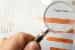 Magnifier op een gekleurde die trechtergrafiek op een wit blad van document tijdens een commerciële vergadering wordt gedrukt Royalty-vrije Stock Foto