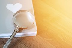 Magnifier over the book on wooden table with light flare and copy space Royalty Free Stock Photos