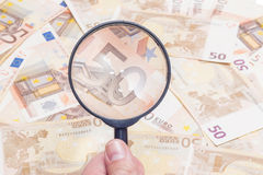 Magnifier over fifty euro notes. Closeup of fifty euro notes through magnifer background Royalty Free Stock Photo