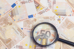 Magnifier over fifty euro notes. Closeup of fifty euro notes through magnifer background Royalty Free Stock Images