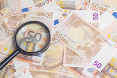 Magnifier over fifty euro notes. Closeup of fifty euro notes through magnifer background Royalty Free Stock Photos