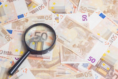 Magnifier over fifty euro notes. Closeup of fifty euro notes through magnifer background Stock Photos