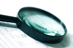 Magnifier over Figures. Magnifying glass over financial figures.  Soft focus, cyan tone Royalty Free Stock Images
