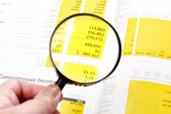 Magnifier over figures Stock Photos