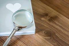 Magnifier over het boek op de houten lijst met exemplaarruimte Royalty-vrije Stock Afbeelding