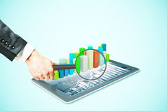 Magnifier over pad with graph. Businessman hand holding magnifier over tablet with voluminous business chart bars. Market analysis concept. Light blue background Stock Photos