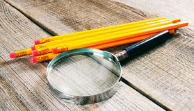 Magnifier and pencils. On wooden background. Stock Photo