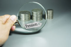 Magnifier, Pension Tag, and Stack of Coins in the backdround Royalty Free Stock Photo