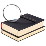 Magnifier and a pile of old books Royalty Free Stock Images