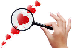 Magnifier and red hearts. Magnifier held by a woman and red hearts Stock Images