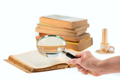 Magnifier search of old books Stock Photo
