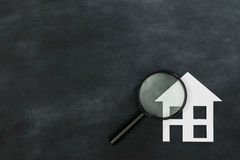 Magnifier searching house isolated on chalkboard. Magnifier searching new house concept isolated on chalkboard background with high angle view photo Royalty Free Stock Image