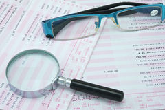 Magnifier and spectacles on bank account. Magnifier and spectacles are on pink and white bank account Stock Photos