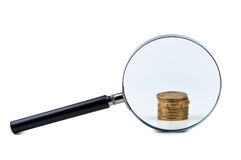 Magnifier and stack of coins. Stock Photography