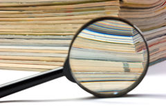 Magnifier and stack of magazines Stock Photo