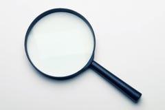 Magnifier su priorità bassa bianca Immagini Stock Libere da Diritti