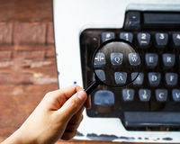 Magnifier on Typewriter. Proofreading concept Stock Photography