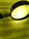 Magnifier and word debt. An image of a magnifying glass focusing on the word debt in a financial document.  Monochrome sepia yellow photograph. Simple Stock Image