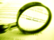 Magnifier and words cash flow. An image of a magnifying glass focusing on the word cash flow in a financial document.  Monochrome sepia yellow photograph. Simple Stock Photography
