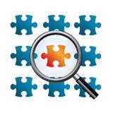 Magnifiez le verre sur le puzzle rouge Photographie stock libre de droits