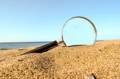 Magnifique el vidrio en la playa de la arena imágenes de archivo libres de regalías