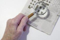 Magnifique el vidrio usado por la vieja persona pobre mayor mayor de la vista y de la visión para el crucigrama fotografía de archivo libre de regalías