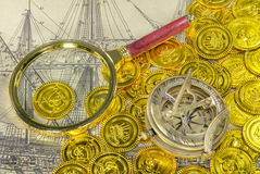Magnify glass compass on a golden pirate coin. A magnify glass compass on a golden pirate coin Royalty Free Stock Photos