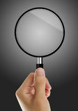 Magnify glass in hand. On gray blackboard Royalty Free Stock Image