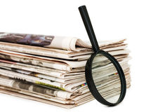 Magnify glass over a stack of newspaper stock images