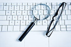 Magnify Glasses on Keyboard. Magnify Glasses on Computer Keyboard, Blue Business Tone Royalty Free Stock Photo