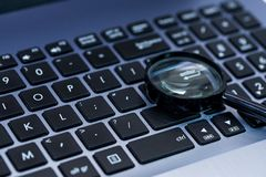 Magnifyer-Glas auf Laptop-Computer Tastatur im blauen Ton, lizenzfreie stockfotografie
