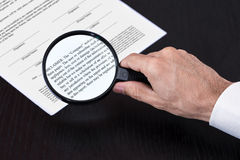 Magnifying class examining footnotes. And small-prints Royalty Free Stock Images