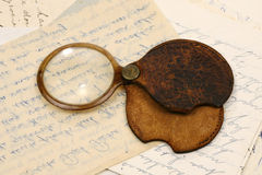 Magnifying glass. A magnifying glass with a cover on old letters Royalty Free Stock Image
