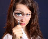 Magnifying Glass. Cute woman with magnifying glass royalty free stock image