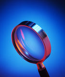 Magnifying glass. With red highlights shot on blue graduated background Royalty Free Stock Photos