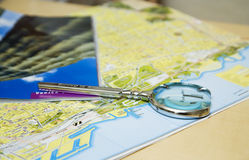 Magnifying glass. Lying on tourist's map Stock Images