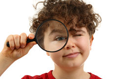 Magnifying glass. Young boy holding magnifying glass isolated on white background Royalty Free Stock Photos