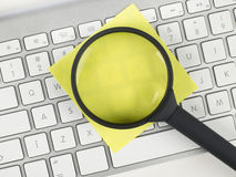 Magnifying glass and adhesive note over a keyboard Royalty Free Stock Image