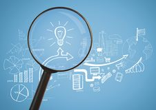 Magnifying glass against blue background with idea bulb and business graphic drawings Stock Photo