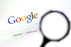 Magnifying glass against Google homepage Royalty Free Stock Photo