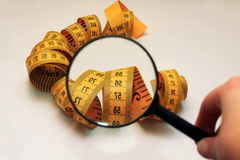 The magnifying glass aimed at measuring tape Royalty Free Stock Images
