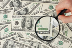 Magnifying glass on american hunderd dollars money Stock Photos
