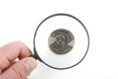 Magnifying glass and  ancient coins Stock Photos