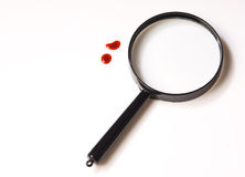 Magnifying Glass And Blood Drops Over White Stock Images
