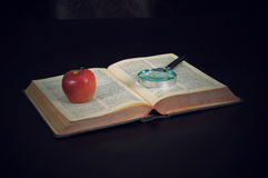 Magnifying glass and apple on the book Royalty Free Stock Image