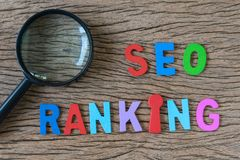 Magnifying glass and arrange colorful alphabets SEO RANKING on w. Ooden table as SEO Search engine optimisation concept Royalty Free Stock Photos