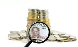 Magnifying glass with background of coins to be dollar, business Stock Photography