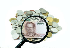 Magnifying glass with background of coins to be dollar, business concept Royalty Free Stock Images