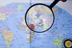 Magnifying glass on the background of the world map and playing pawns Royalty Free Stock Image