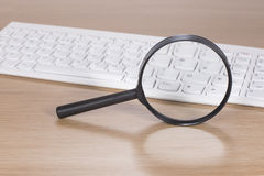 Magnifying glass balanced upright near a keyboard Stock Photos